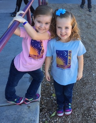 Two young girls wearing t-shirts with the Or Chadash logo, one pink and one blue.